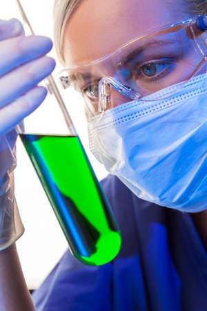 A female medical or scientific researcher or doctor looking at a green solution in a laboratory  photo