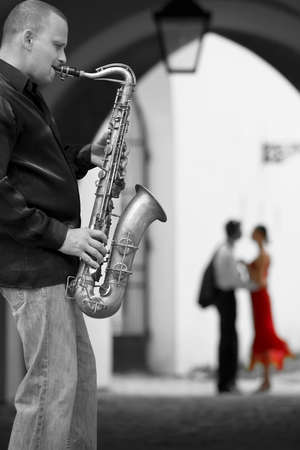 Black and white photograph street musician playing his saxophone while a romantic couple can be seen out of focus in the background the woman is in color wearing a red dress photo