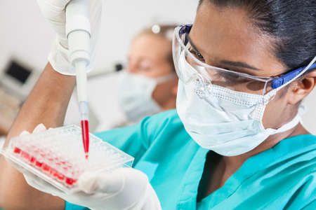 A female Asian medical or scientific researcher or doctor using a pipette and sample tray to test blood sample in a laboratory with her blond female colleague out of focus behind her. photo