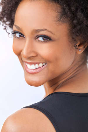 A beautiful mixed race African American girl or young woman looking happy and smiling with perfect teeth Stockfoto