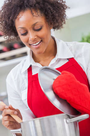 mixed race woman: A beautiful mixed race African American girl or young woman looking happy wearing red apron   cooking in her kitchen at home Stock Photo