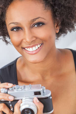 A beautiful mixed race African American girl or young woman looking happy taking pictures or photographs with a retro digital camera photo