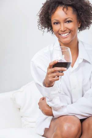 A beautiful happy mixed race African American girl or young woman wearing a white shirt and drinking red wine at home on a sofa photo