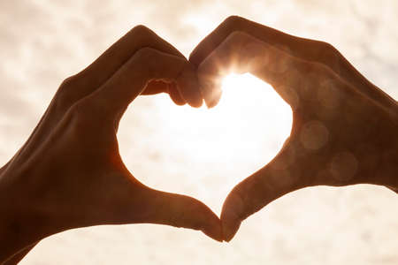silhouette coeur: silhouette en forme de coeur � la main fait contre le ciel de soleil d'un lever ou coucher de soleil Banque d'images