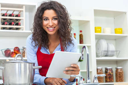 A beautiful happy young woman or girl wearing a red apron   using a tablet computer while cooking in her kitchen at home Banque d'images