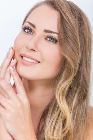 Portrait of a beautiful blond young woman with green eyes smiling and touching her face with her hands photo