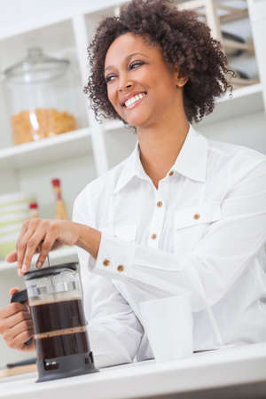 making coffee: A beautiful happy mixed race African American girl or young woman making coffee with a cafetiere in her kitchen at home