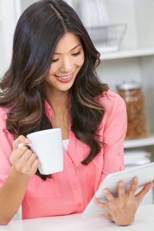 Beautiful Asian Chinese Woman Using Tablet Computer and drinking tea or coffee at home in her kitchen photo