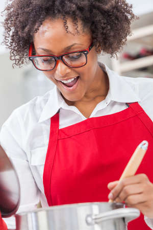 stirring: A beautiful mixed race African American girl or young woman looking happy wearing glasses a red apron   cooking in her kitchen at home