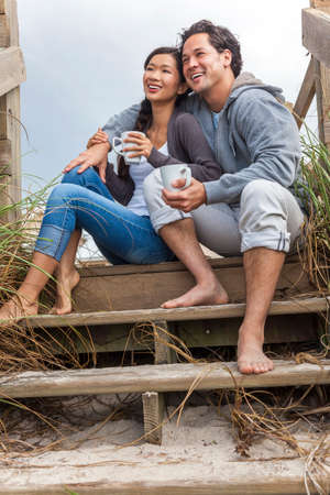 Young Asian Chinese man & woman, boy & girl, couple sitting on wooden steps overlooking a beach drinking mugs of tea or coffee photo