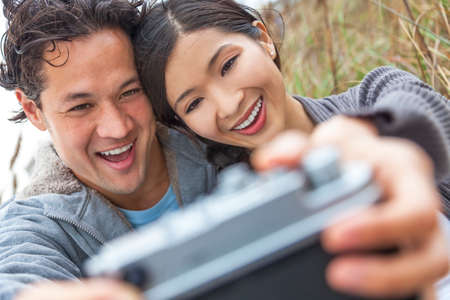 Young Asian Chinese man & woman, boy & girl, couple sitting in the sand dunes on a beach taking a selfie photograph with retro style digital camera photo
