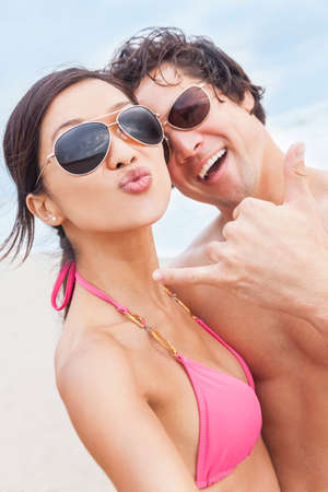 Man & woman Asian couple, boyfriend girlfriend in bikini, taking vacation selfie photograph at the beach