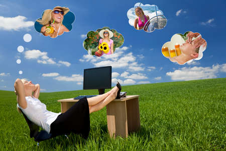 Business concept shot of a beautiful young woman relaxing at a desk in a green field day dreaming, of being on holiday. Dream clouds fill the blue sky.  Stockfoto