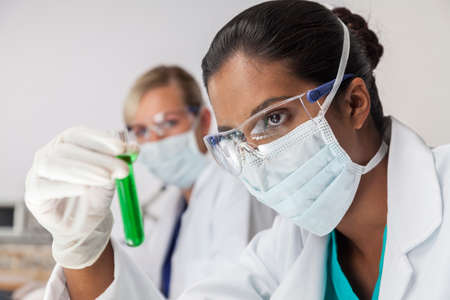 An Asian medical or scientific researcher or doctor using looking at a test tube of green liquid in a laboratory with her female colleague out of focus behind her. photo