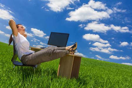 Business concept shot of a beautiful young woman businesswoman relaxing at an office desk   computer in a green field with a bright blue sky   white clouds  photo