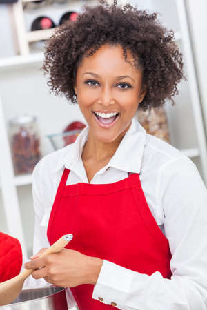 stirring: A beautiful mixed race African American girl or young woman looking happy wearing a red apron   cooking in her kitchen at home