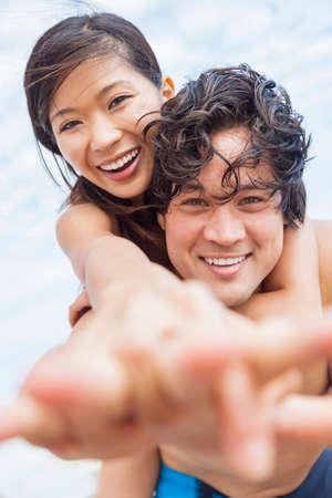 Man & woman Asian couple, boyfriend girlfriend in bikini, taking vacation selfie photograph at the beach  photo