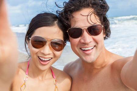 hot guy: Man & woman Asian couple, boyfriend girlfriend in bikini, taking vacation selfie photograph at the beach