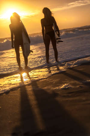 Beautiful young women surfer girls in bikinis with surfboards on a beach at sunset or sunrise photo
