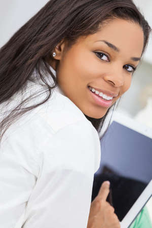Beautiful happy young African American woman or girl smiling and using a tablet computer photo