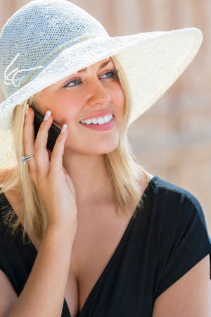black hair blue eyes: A beautiful girl young female woman with blond hair & blue eyes talking on her cell phone wearing white sun hat and little black dress