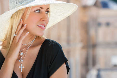 sun hat: Beautiful blonde girl young woman wearing white sun hat, silver jewelry crucifix necklace and little black dress