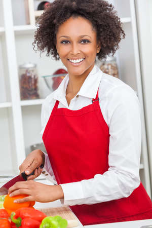 A beautiful mixed race African American girl or young woman looking happy wearing red apron, chopping vegetables & cooking in her kitchen at home photo