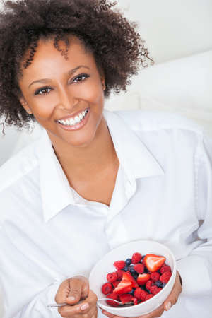 sexy food: A beautiful mixed race African American girl or young woman looking happy and eating fruit salad in a bowl, raspberries, strawberries & blueberries Stock Photo
