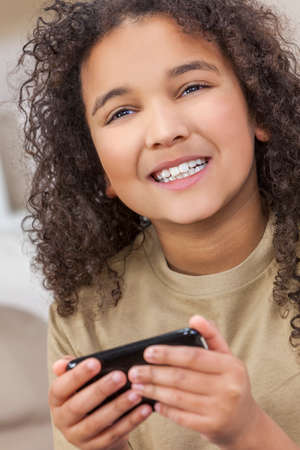 Beautiful young mixed race interracial African American girl child smiling with perfect white teeth using smart cell phone for texting or playing video games photo