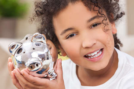 american money: Beautiful happy young mixed race interracial African American female girl child smiling and holding a silver young saver piggy savings money bank Stock Photo