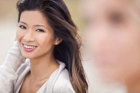 smile faces: Outdoor portrait of a beautiful happy smiling Chinese Asian young woman or girl at beach with blond female friend out of focus in foreground