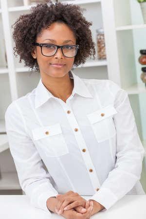 fille noire: Une belle m�tisse afro-am�ricaine fille intelligente noir ou jeune femme air heureux et portant des lunettes de geek dans la cuisine � la maison