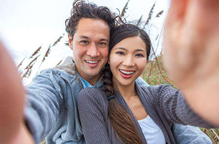 Man & woman Asian couple, boyfriend girlfriend in bikini, taking vacation selfie photograph at the beach  photo