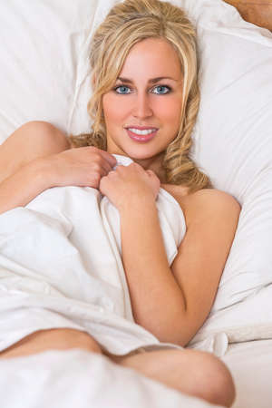 blue eyed: A beautiful blond haired blue eyed young woman and wrapped in white sheets on her bed