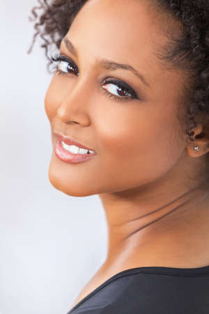A beautiful mixed race African American girl or young woman looking happy and smiling with perfect teeth photo