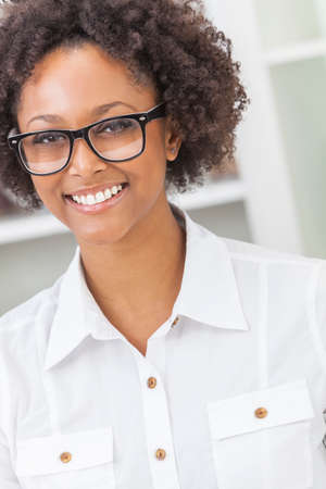 mixed race people: A beautiful intelligent mixed race African American girl or young woman looking happy and wearing geek glasses