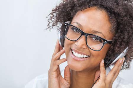 musica electronica: Una hermosa niña de raza mixta afroamericana o una mujer joven que llevaba gafas y escuchar música en el reproductor de mp3 y auriculares Foto de archivo