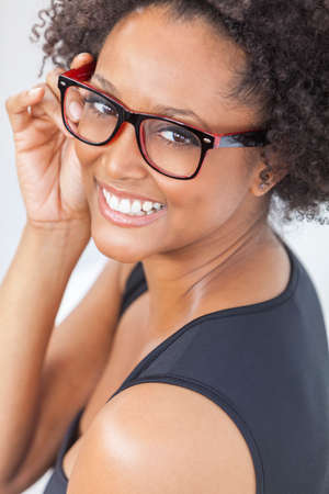 women glasses: A beautiful intelligent mixed race African American girl or young woman looking happy and wearing geek glasses