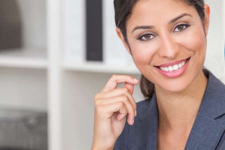 Portrait of a beautiful young Latina Hispanic woman or businesswoman wearing smart business suit in her office photo