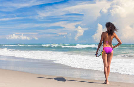 attractive ass: Rear view of beautiful young woman surfer girl in bikini with surfboard standing in the surf on a beach