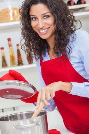 sexy black girl: A beautiful girl or young woman looking happy wearing red apron & cooking in her kitchen at home