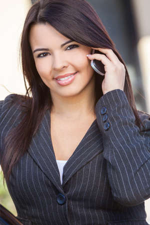 Beautiful happy young Latina Hispanic woman or businesswoman smiling and talking on her cell phone outside photo