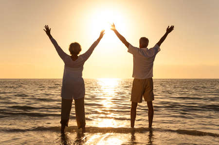 Senior man and woman couple arms raised celebrating together at sunset or sunrise on a beautiful tropical beach photo