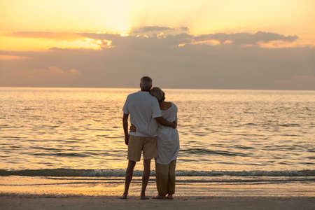 Senior man and woman couple embracing at sunset or sunrise on a deserted tropical beach photo