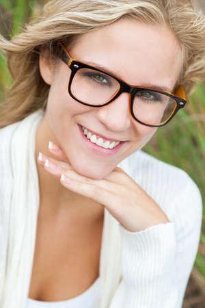 jolie fille: Sourire heureux belle jeune femme ou fille blond portant des lunettes de geek en dehors