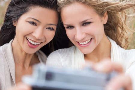 lesbianas: Dos jóvenes mujeres niñas, un chino de Asia, una rubia, riendo fotografía Autofoto toma con cámara digital