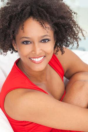Een mooi gemengd ras Afrikaans Amerikaans meisje of jonge vrouw draagt een rode jurk op zoek gelukkig en lachend met perfecte tanden