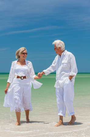 Happy senior man and woman couple walking, laughing and holding hands on a deserted tropical beach with bright clear blue sky photo
