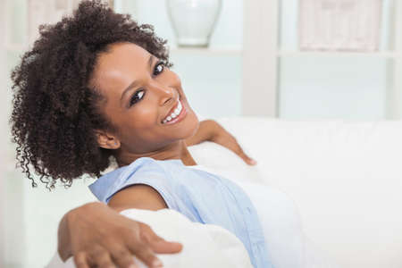 A beautiful mixed race African American girl or young woman sitting on sofa at home looking happy and relaxed Stockfoto