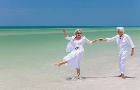 Happy senior man and woman couple dancing, holding hands & splashing in sea water on a deserted tropical beach with bright clear blue sky 免版税图像